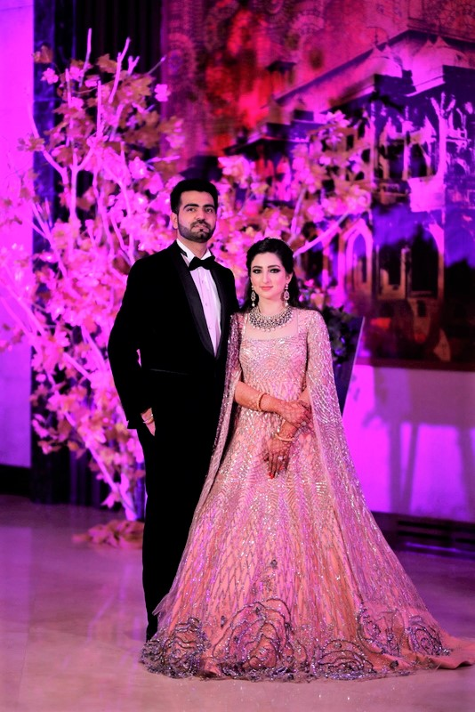Bride in pink bridal gown & groom in black suit