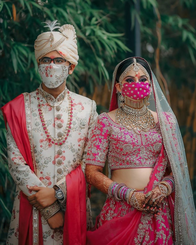 Indian bride & groom coordinates wedding face masks with their wedding outfits