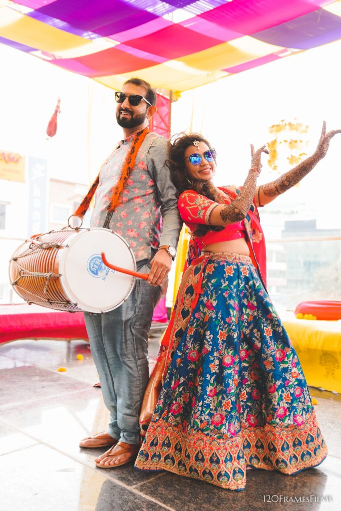 Indian bride &groom in colorful mehendi outfits